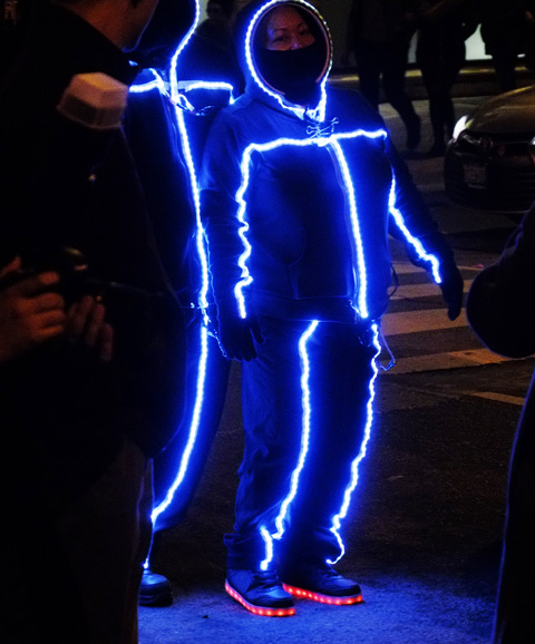 two people in jogging suits with hoods, with lights down the front so it looks like stick people