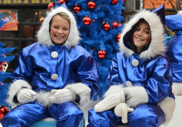 two girls on a float at the Santa Claus parade, dressed in shiny blue clothes with fuzzy white furry trim, smiling and looking at the camera