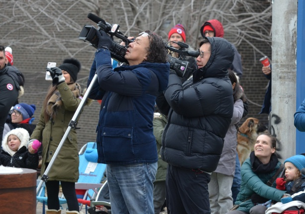 two camera men with large video cameras filming the Santa Claus parade