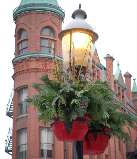 Christmas decorations, pine branches and red plant pots, on a lamp post in front of the Gooderham building in Toronto, red brick flatiron type building