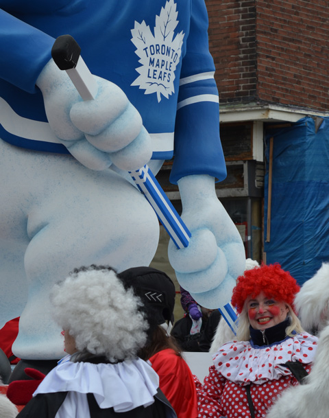 a clown in red polka dot clothes and bright red wig, smiles as she stands beside a float at Santa Claus parade with a large Carlton Bear, the Toronto Maple Leafs mascot