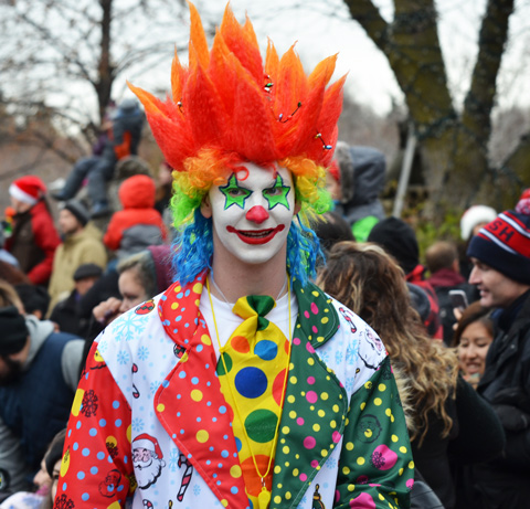 a clown with bright orange hair and a multi coloured outfit, in front of a crowd outside