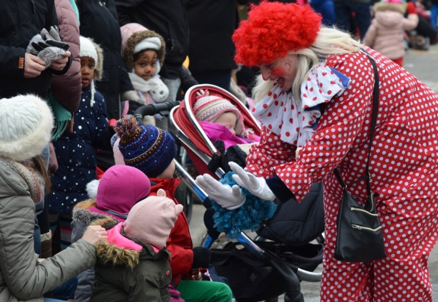 a clown in polka dot outfit and red wig bends down to high five with kids on the sidewalk who are watching the parade