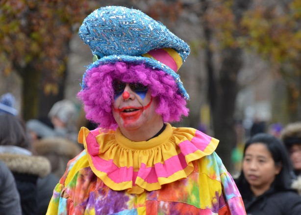 a male clown in pink wig and pink and yellow ruffle collar, large floppy blue hat and lots of make-up on his face