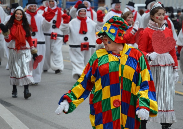 a clown with a bright red nose walks in a parade, in front of people dressed as snowmen with red scarves and black belts, clown has a chequered outfit on, in primary colours plus green