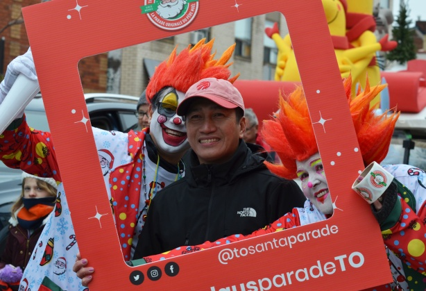 a man poses in an instagram frame that is being held by two clowns with bright orange hair