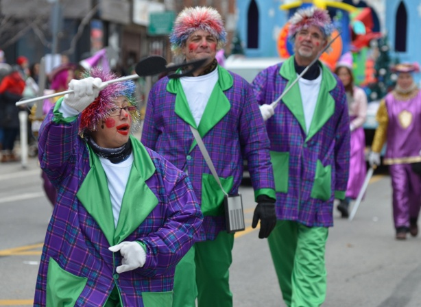 clowns in purple and green outfits and many colours in their wigs, walking in Santa Claus parade