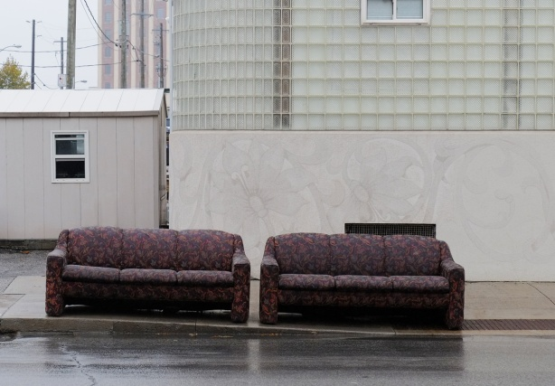 two burgundy sofas on the sidewalk