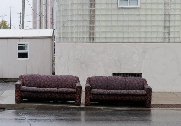 two burgundy sofas on the sidewalk