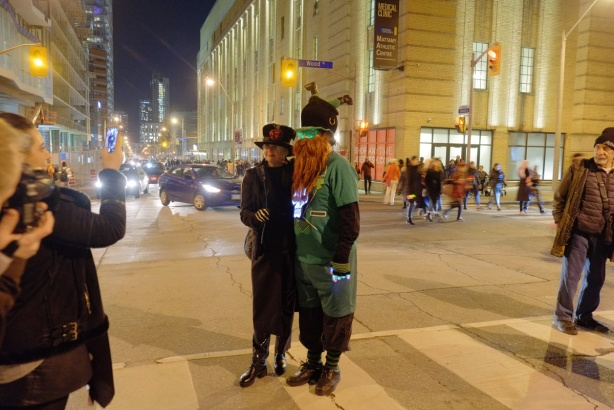 couple posing for pictures at the corner of Church and Wood, both are dressed in Halloween costumes, night time,