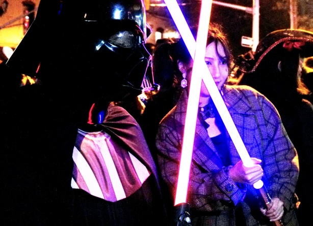 a woman crosses light sabres with darth vader, hallowwen party on Church St. in Toronto