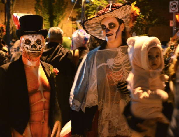 Church Street, Halloween party, a couple in costumes suitable for day of the dead celebrations, juxtapositioned with a man holding a baby