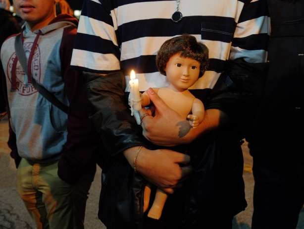 a man in a black and white striped shirt is holding a doll and a lit candle