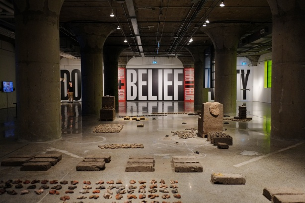 inside MOCA (Museum of Contemporary Art) which is an old industrial building, with original concrete columns, art installation on the floor and another on the far wall. On the wall are large words doubt, belief, and sanity.