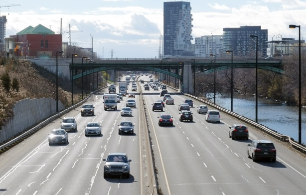 looking south from a bridge over the Don Valley Parkway road, with cars driving north and south, looking towards bridge at Dundas Street, Don River to the right,