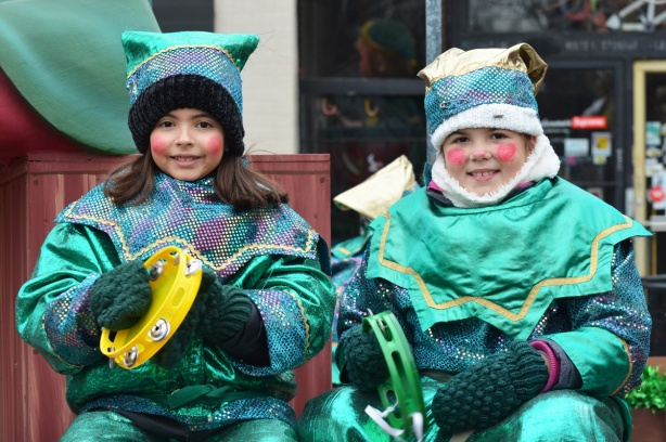 two girls sitting together on a float at the Santa Claus parade, shiny green and purple costumes