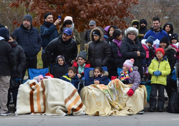 a group of people on the sidewalk watching a parade, kids in front on chairs and under blankets, parents behind standing.
