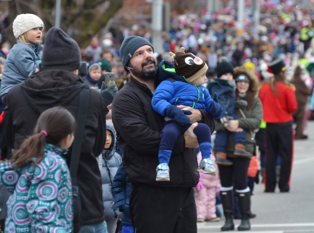 a father holds a toddler son in his arms, outside, beside the street, with crowds watching parade, winter, warm coats and hats