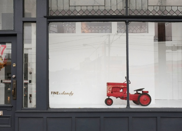 a red toy tractor, old fashioned, in the window of fine and dandy on Dundas Street, white back drop behind the tractor, the building is dark grey