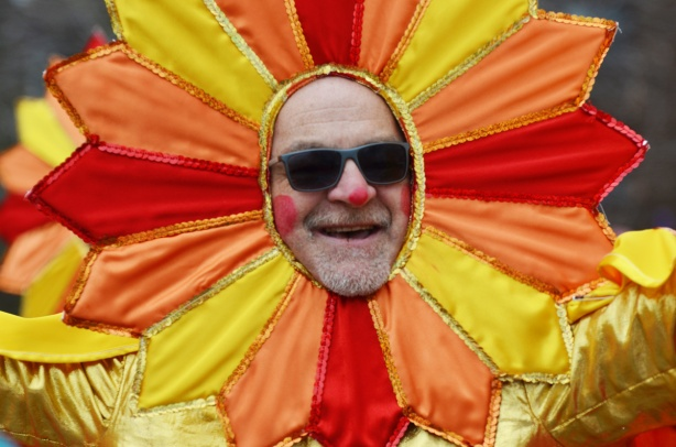 man's face, wearing sunglasses in the middle of an orange and yellow flower, part of Santa Claus parade
