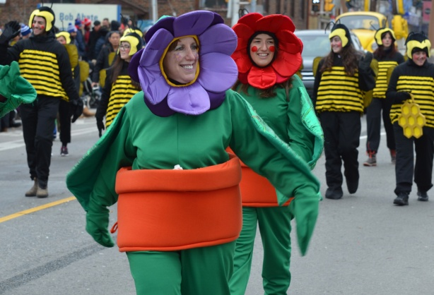 two women are dressed as flowers in terra cotta flower pots, walking down the street in a parade, followed by some people dressed in black and yellow bumble bee costumes