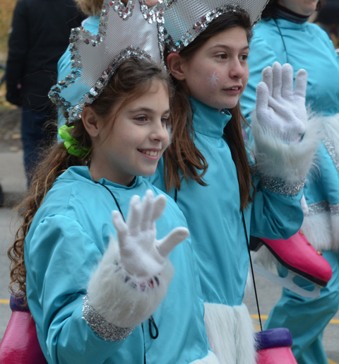 two girls waving to the crowd as they walk in a parade, white gloves, turquoise outfits, shiny star shaped crowns on their heads