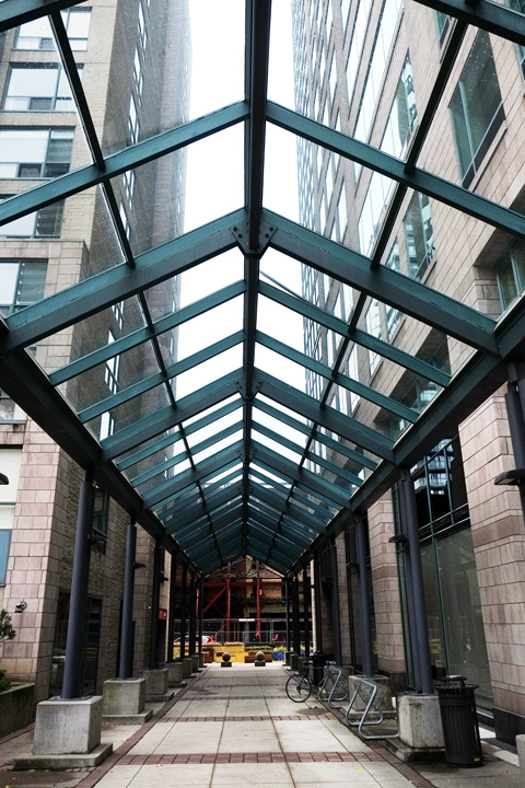 glass and metal covering over a walkway outside between two buildings
