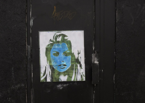 a paper paste up of woman's face in green and blue (green skin and blue hair) on a very black wall and door