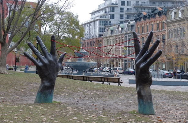 "sculpture of two black hands, very large, reaching out of the ground, with red rope ""cat's cradle"" between them, fountain in the background, Berczy park in Toronto"
