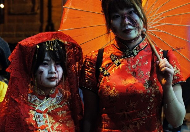 two women in elaborate embroidered red silk kimonos, one with a parasol too, one with a make up gash on her cheek
