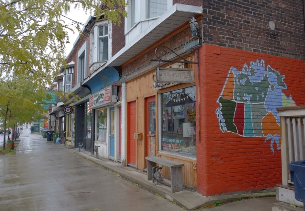 row of stores on Dundas Street, one on the end has a map of Canada painted on the exterior wall, with orange background.