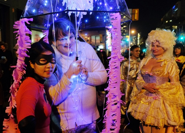 two people standing under a clear umbrella with little lights dangling from it, one person has a black mask on and a costume like the invincible movie character