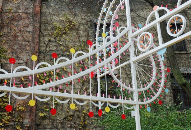 part of a white metal sculpture of a treble clef and a line of music, with yellow and red lights, in a garden, in a city with a brick wall behind it