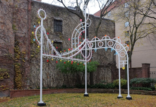 a white metal sculpture of a treble clef and a line of music, with yellow and red lights, in a garden, in a city with a brick wall behind it