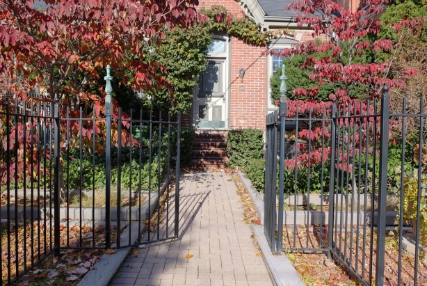 a wrought iron fence and open gate in front of a brick house built in the workers cottage, or gothic cottage, style. Red leaves on burning bushes type shrub on either side of path leading to front door