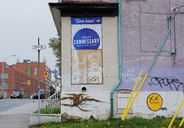 building on the corner of Perth Ave and Bloor West, pale purple paint, a bright yellow happy face graffiti, a sign advertising Drake Commissary