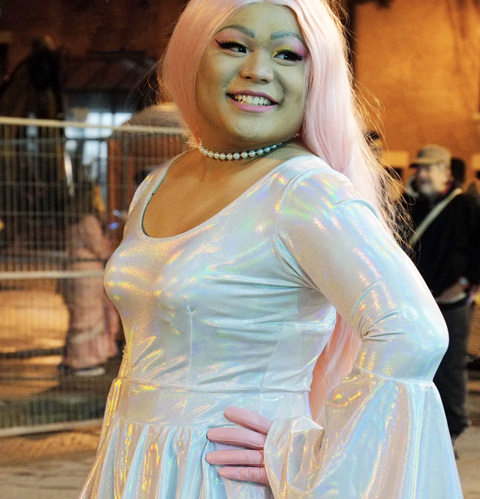 a person with a pale pink wig and shimmering fabric dress