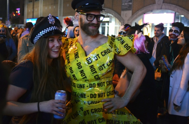man dressed in a dress that is made of yellow police caution tape, also wearing a police cap. Posing with a woman who is also wearing a poilce hat