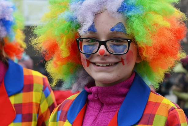 young woman with rainbow wig, and bright coloured clothes, clown in a parade