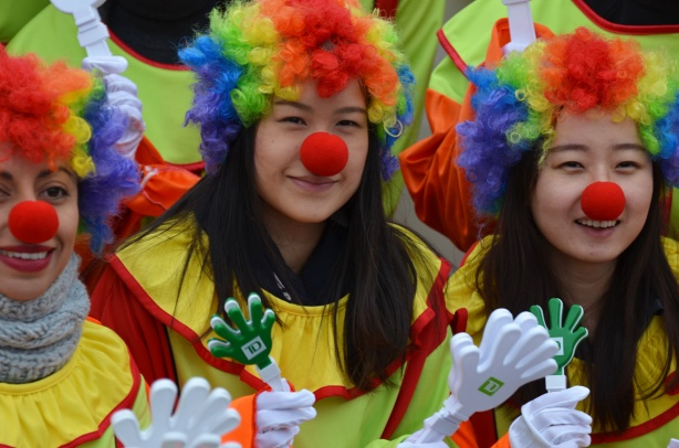 3 girls dressed as clowns with rainbow wigs, and big red noses.