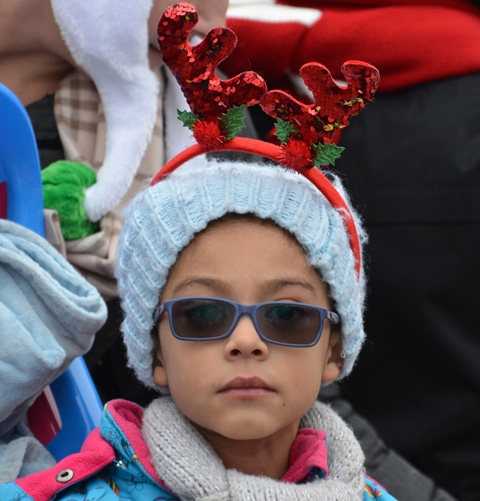 girl with hat with shiny red reindeer ears, also sunglasses