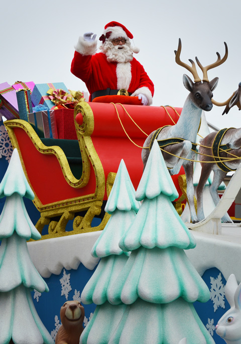 Santa Claus stands in his sleigh that is being pulled by reindeer on the top of a float in the Santa Claus parade.