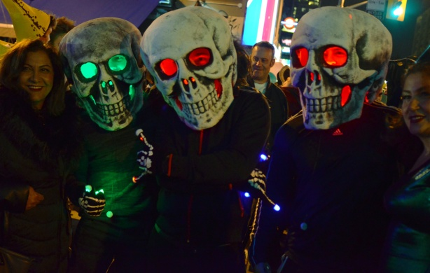 two women pose with three people wearing oversized skulls on their heads, with lights inside that make the eyes appear bright, two red eyed skulls and one with green eyes