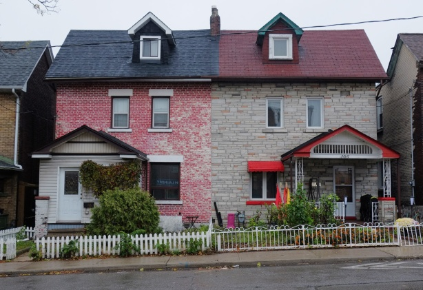 two attached houses in the Junction, one painted red brick with dark blue roof and the other light brown with dark red roof and bright red trim, small white picket fence in front of the red house, metal fence in front of the brown house (beige actually)