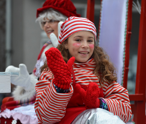 a girl in red and white striped hat and outfit, and red mitts, sits on a float in the Santa Claus parade and waves to the crowd