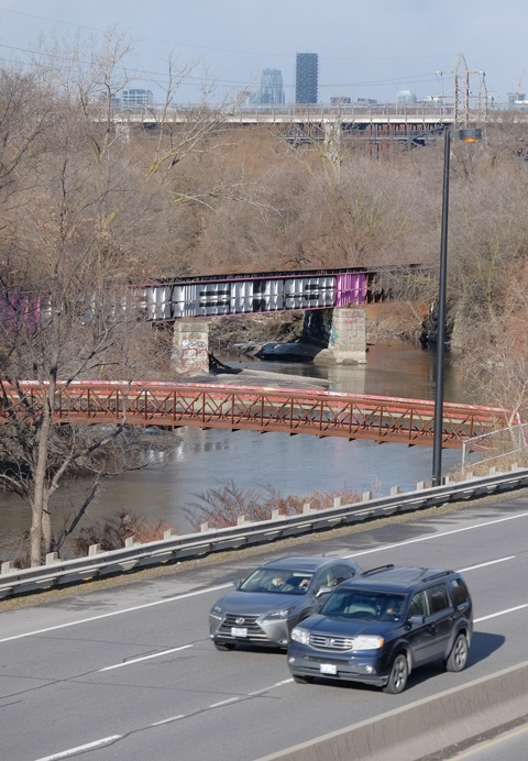 two cars driving on the Don Valley Parkway, past the Don River and two bridges over the river. In the distance is the Bloor Viaduct, trees, and some apartment buildings.
