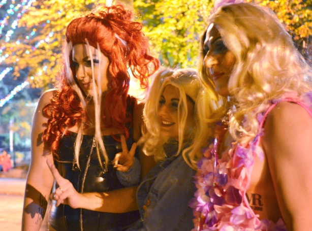three people in big long haired wigs, one red head and two blondes