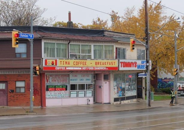 restaurant and store, rainy day, wet sidewalk and street in front of it, Tina Coffee and Breakfast restaurant, and Tommys Gift & Variety, pink door between the two, two storeys, lots of windows in the storey above Tina's.