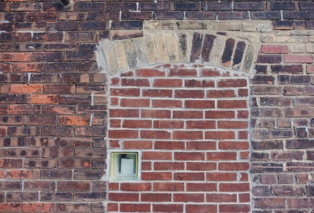 a brick wall, an old arched window has been bricked in, leaving a small window, in the window is a roll of toilet paper