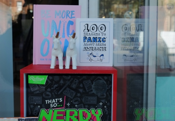 in a shop window, two toy unicorns, a book about unicorns, and a book about the 100 things about being awesome